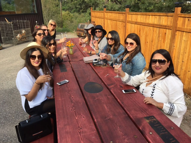 Several women tasting wine at large table on wine tour